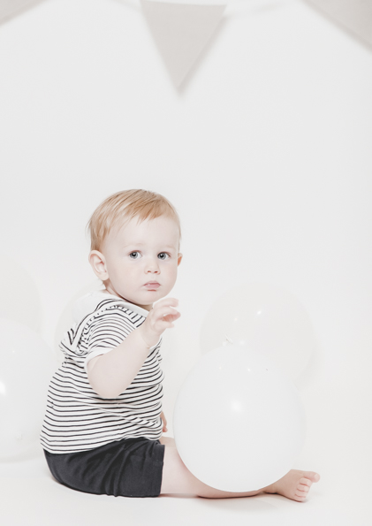 Minimal, bright and airy first year birthday photography of baby boy on white background studio set up